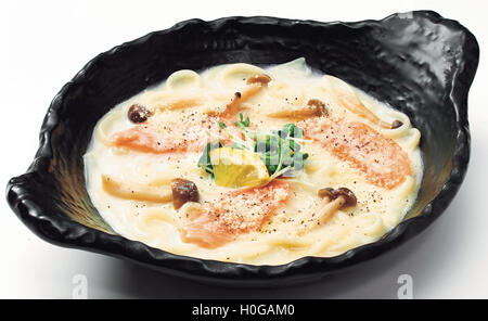 Japanese Udon noodle with salmon, mushroom, lemon and sprout in black bowl - Stock Photo