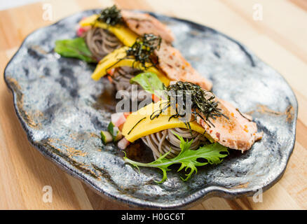 Salmon Soba with noodle, herbs and seaweed on black platter - Stock Photo
