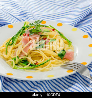 Pasta noodle with sauteed pork and vegetables on the tablecloth - Stock Photo