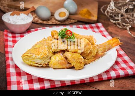 Plate of fried fish on the table in restaurant - Stock Photo