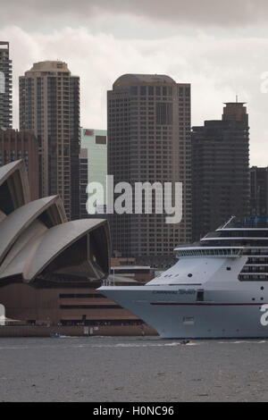 The Carnival Spirit Cruise Ship passes directly in front of the Sydney Opera House as she departs Sydney Australia - Stock Photo