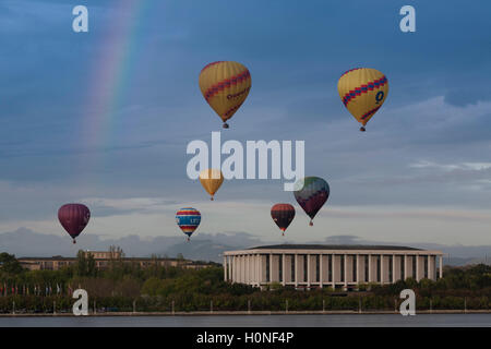 Hot air balloons passing over Lake Burley Griffin and Australian National Library during the balloon festival Canberra - Stock Photo