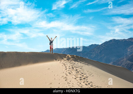 Young man standing on sand dune, Mesquite Flat Sand Dunes, Death Valley, Death Valley National Park, California, - Stock Photo