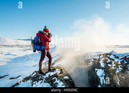 Woman standing at divergent tectonic boundary between North American and Eurasian plates, photographing, Mid-Atlantic - Stock Photo
