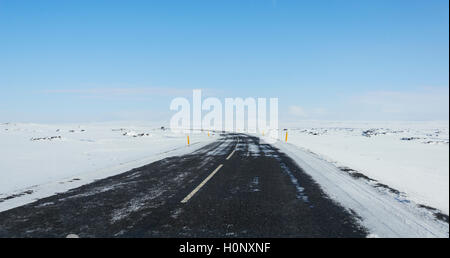 Road through snowy landscape, ring road, National Highway 1 or Hringvegur, North Island, Island - Stock Photo