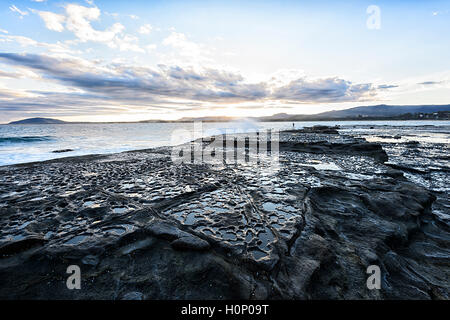 View of a sunset over the rock shelf at Gerroa Headland, Shoalhaven, New South Wales, NSW, Australia - Stock Photo