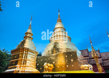 Dusk View of the golden stupa of Wat Phra Singh temple, the most revered temple in Chiang Mai, Thailand. - Stock Photo