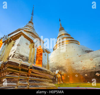 Dusk View of the golden chedi (stupa) of Wat Phra Singh temple, the most revered temple in Chiang Mai, Thailand. - Stock Photo