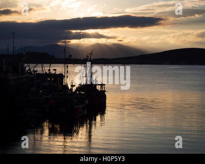 Sunset over the Mountains of Mull from Oban Harbour Argyll and Bute Scotland - Stock Photo