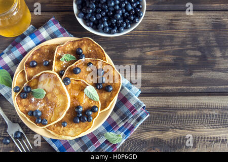 Pancakes on plate with blueberries, mint and honey for breakfast - homemade healthy vegetarian food - Stock Photo