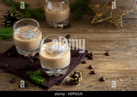 Irish cream coffee liqueur with ice, Christmas decoration and ornaments over rustic wooden background - homemade festive drink