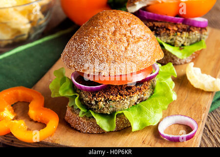 Vegetarian lentil burger with vegetables on wooden cutting board - healthy tasty vegetarian snack (food, lunch) - Stock Photo