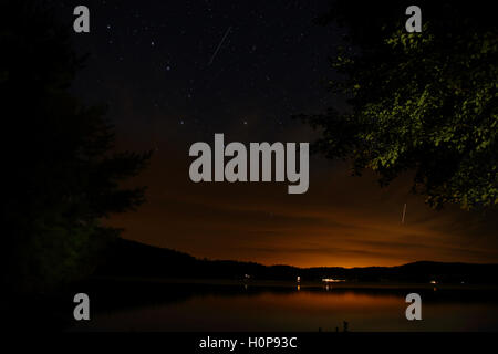 August night sky with stars and a meteor trail through the Big Dipper constellation over a Lake Hortonia in western - Stock Photo