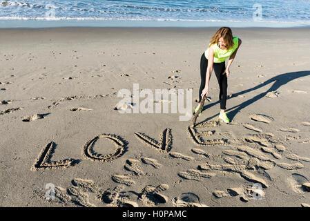 The word love written on the beach sand - Stock Photo