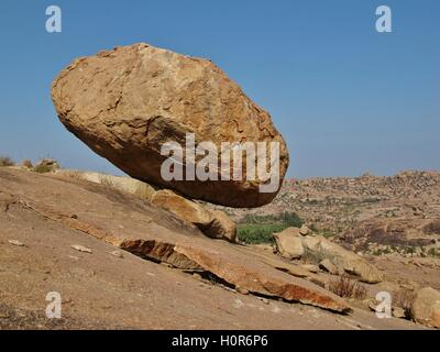 Big balancing granite boulder in Hampi, India. Giving a impression of hovering above the ground. - Stock Photo
