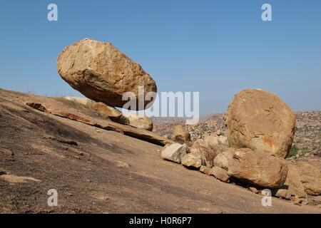 Stunning scene in Hampi, India. Big granite boulder balancing on a little edge. - Stock Photo