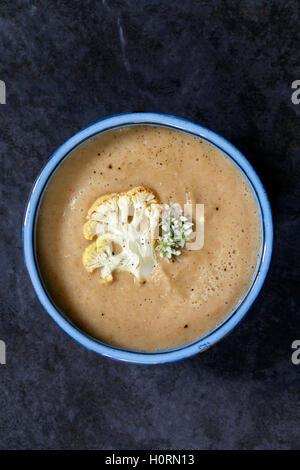 Roast cauliflower soup with wild garlic flowers - Stock Photo