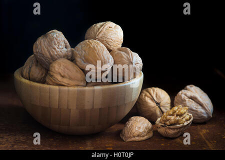 Wooden bowl with walnuts on a dark background - Stock Photo