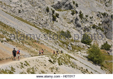 People hikers walking along Cares Gorge route between towns of Poncebos and Cain in Picos De Europa National Park - Stock Photo