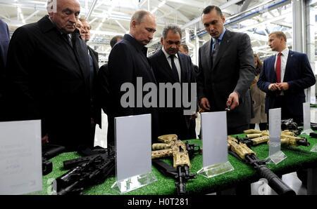Russian President Vladimir Putin accompanied by Defense Minister Sergei Shoigu, center, views weapons manufactured - Stock Photo