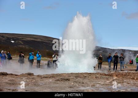 tourists stand around watching the strokkur geyser to erupt geysir Iceland - Stock Photo