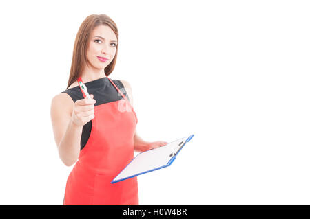 Smiling young seller pointing you with pen and holding clipboard on white background with advertising area - Stock Photo