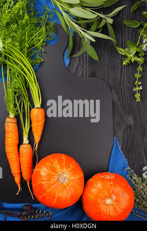 Carrots, pumpkin, sage, basil and thyme on a blackboard and a blue towel top view with copy space