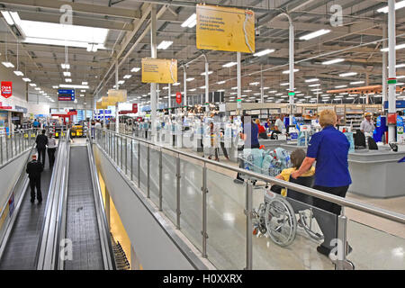 Disability customer service staff & inclined travellators in Tesco supermarket store to access shopping floor from - Stock Photo