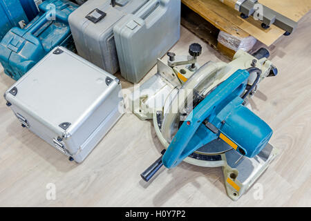 Various plastic tool boxes are on laminate floor with a lot of equipment for furnishing in workshop. - Stock Photo