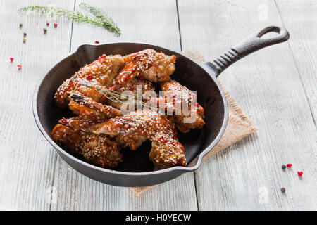 Chicken wings in cast-iron pan on wooden table. Marinated in tomato and honey sauce. Baked with sesame seeds. - Stock Photo