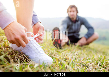 Couple running in autumn nature, stretching, tying shoelaces - Stock Photo