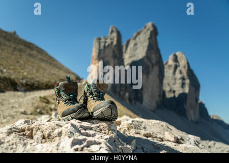 Boots to the mountains for hiking on the background of the Dolomites region Tre Cimme, Italy. Hiking shoes of a - Stock Photo