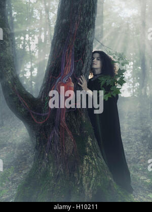 Woman druid in the forest listening to the heartbeat of a tree, artistic conceptual photo illustration. - Stock Photo