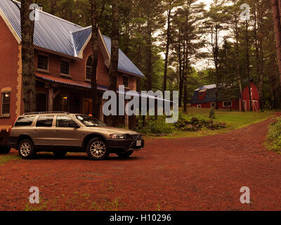 Brick country house or cottage and Volvo XC70 station wagon car in Muskoka, Ontario, Canada countryside scenery. - Stock Photo