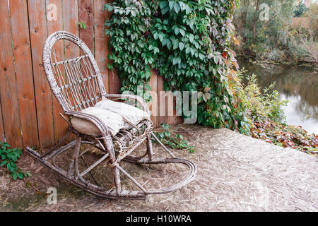 old rocking chair on the front porch of an  house. wooden wall with vine grapes - Stock Photo