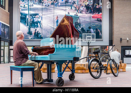 Man plays piano towed by bicycle  Keys to the Streets Piano, Woodward's Atrium, Vancouver,  British Columbia, Canada - Stock Photo
