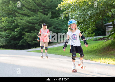 Happy, young girl on roller skates, skating toward viewer, smiling, and looking into camera.  Overseen by woman - Stock Photo