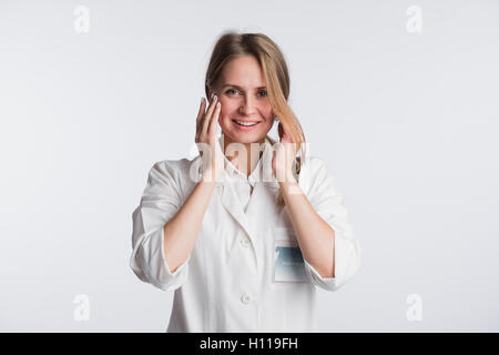 Young female doctor or nurse is shocked with hands on her mouth - Stock Photo