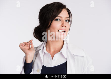 Young woman with a tablet pill in the mouth - Stock Photo