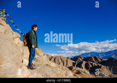 Young Asian traveler standing on high hills and looking away at the village over blue sky background in Leh, Ladakh, - Stock Photo