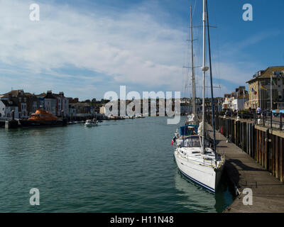 Yachts and lifeboat moored in Weymouth harbour Dorset England UK  view across Old Harbour to Nothe Parade in this - Stock Photo
