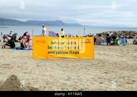 RNLI safety banner on the beach in summer at Lyme Regis, Dorset, England UK    KATHY DEWITT - Stock Photo
