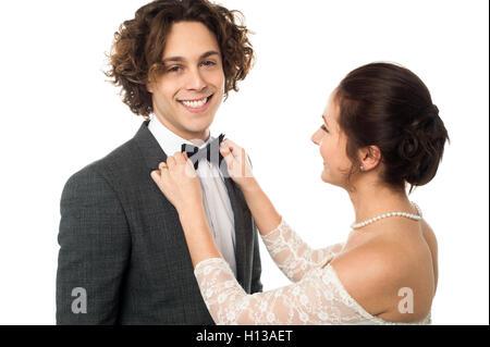 Bride adjusting her man's bow tie - Stock Photo