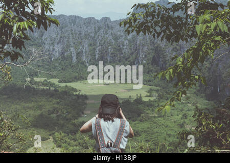 Woman backpacker shoot photo in nature background. - Stock Photo