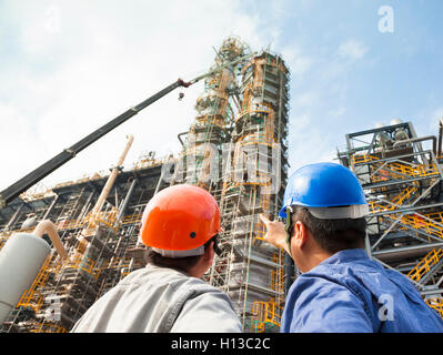 two Factory workers discussion and pointing for inspection - Stock Photo