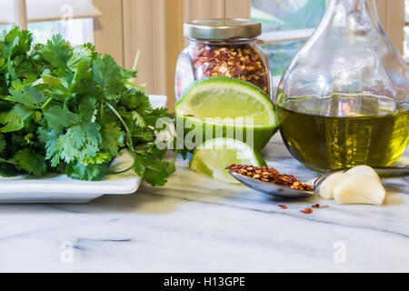 Mexican food ingredients in a kitchen on a marble top . Cilantro red pepper flakes lime garlic olive oil - Stock Photo
