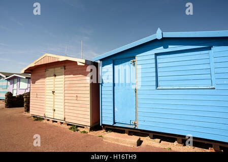 Pink and blue beach huts with nobody present in the summer scene. The doors and windows are sealed shut. - Stock Photo