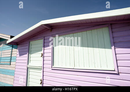 Pink painted wooden beach hut in summertime sunshine. - Stock Photo