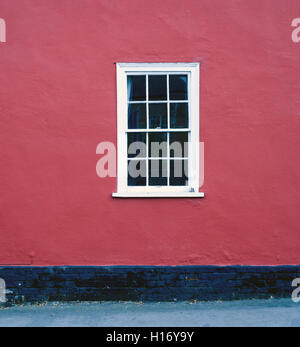 Single White Framed Window Set Against A Red Painted House Brickwall
