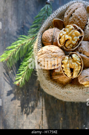 walnuts in a bag on a wooden background - Stock Photo